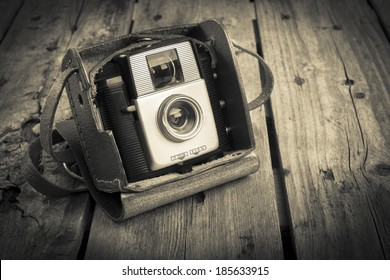 An old camera in its original vintage leather case on a wooden background filtered