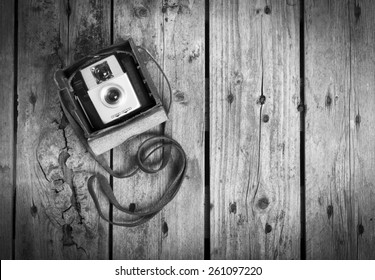 An old camera in its original vintage leather case on a wooden background in black and white