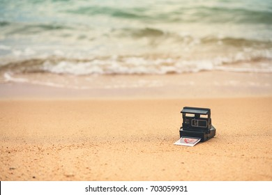 The old camera and picture of memory was left at the beach by the sea. add grain to vintage tones.