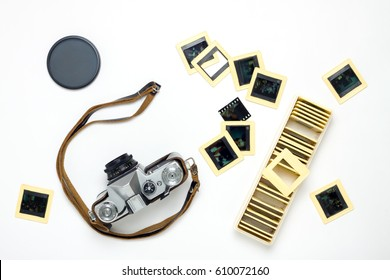 Old camera, slides and polarizing filter flat lay on white