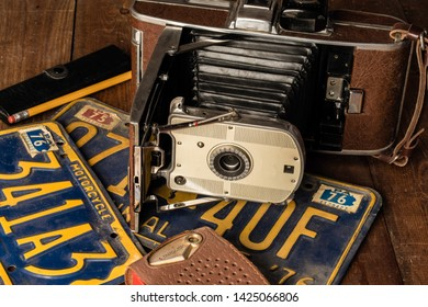 old camera and old transistor radio on  license plates  pencil reading glasses case on wood table