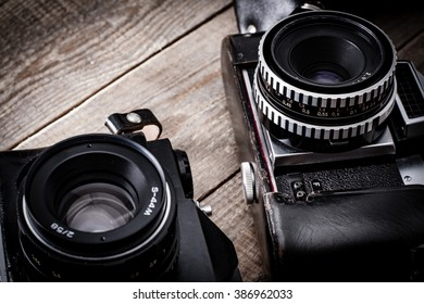 Old cameras with lenses and leather case on wooden table.