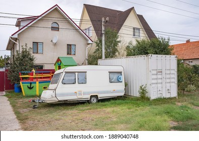Old camping trailer parked near village houses