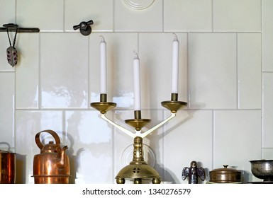 Old candelabrum and other vintage objects standing on the ledge of room heating stove covered with glazed tiles.
