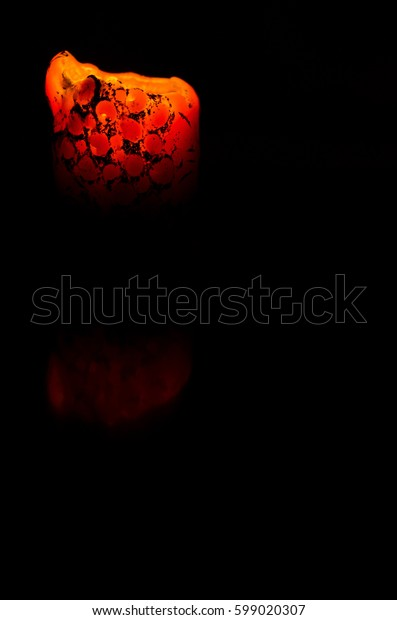Old candle burning on a black background