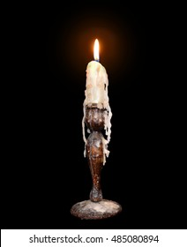 An old candle in a holder with melted wax dripping down the sides, isolated on black.