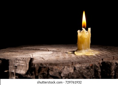 old candle stands on the stump of a tree on the black background
