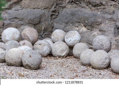 Old cannonballs of gray stone lying on the pebbles at the foot of the rock.