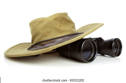 Old canvas hikers hat with a pair of vintage binoculars on white