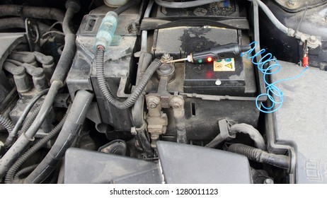 Old car battery with electrolyte drips and probe tester with lamp - repair of car electrical equipment