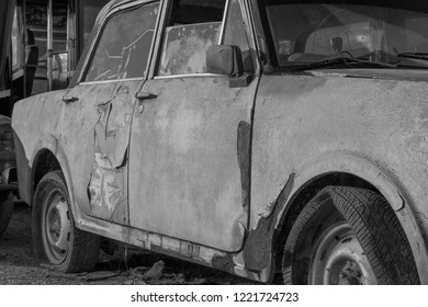 old car in a junkyard black and white