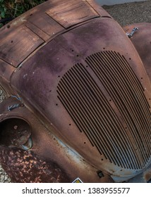 Old car lies rusting away. Tpp far gone to care.