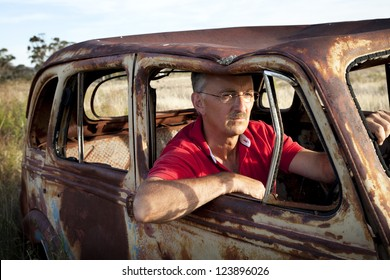 Old car, man in his 50's behind the wheel of a rusted out, vintage type car in an Australian field.