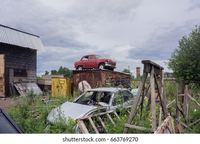 The old car is on the roof of the barn among the dumps