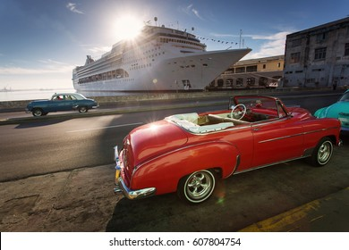Old car on street of Havana at sunrise with cruise ship in background, Cuba