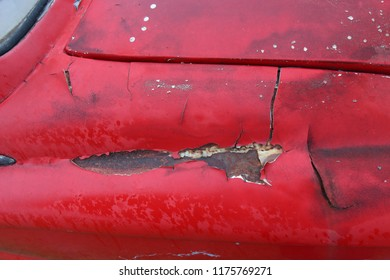 The old car paint cracked red color crack with steel rusty inside