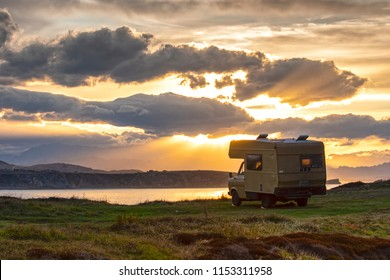 old caravan  at dusk in front of the coast-line
