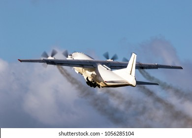 Old cargo airplane taking off with turboprop engine smoke emission.