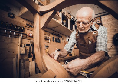 An old carpenter takes measurements at a chair to be restored, a workshop with tools in the background.