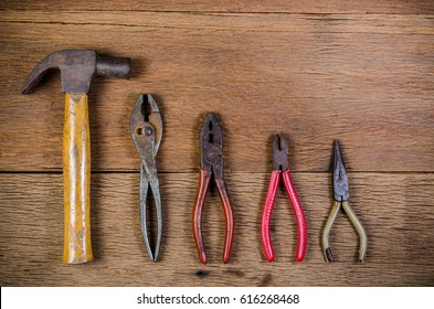 Old carpenter tools on wooden background,rust pliers