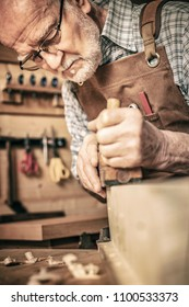 old carpenter uses a planer