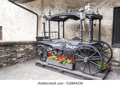 Old Carriage isolated on the old boyard with flowers alone