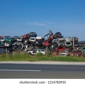 Old cars near road on junkyard are waiting for recycling