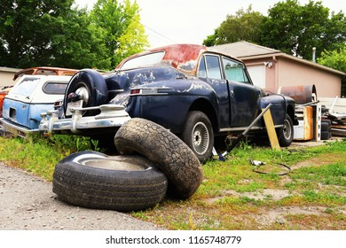 Old cars in various states of repair behind a residential garage