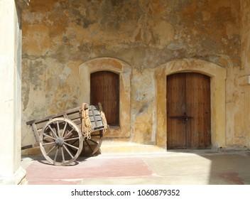old cart next to two wooden doors, Castillo San Cristobal fortification, San Juan, Puerto Rico, Caribbean