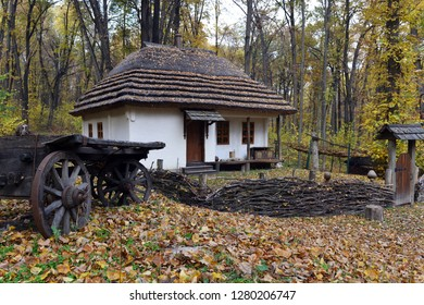 Old cart on the background of the house in the woods. Autumn landscape in the forest.