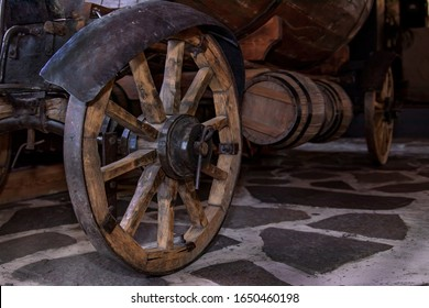 An old cart on wooden wheels for transporting wine barrels.
