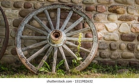 Old cartwheel by the stone wall of an old building