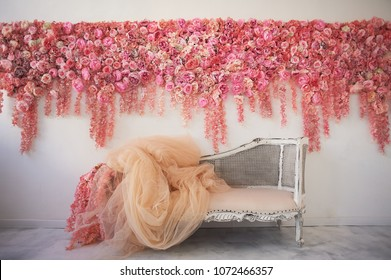 Old carved daybed with soft upholstery against a white wall decorated with pink flowers. Gorgeous garland. The interior decor is romantic, wedding photo zone.