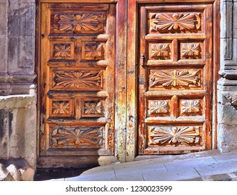 old carved wooden door to a house from the outside, consisting of carved caskets and traditional patterns of the canes, the wood is weathered by the rain and sun bleached
