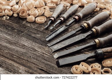 Old carving and woodworking tools and wood shavings on a vintage workbench: carpentry, woodworking and craftsmanship concept