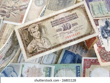 Old cash money from different countries around the world. With old Dinaras from Yugoslavia on top.