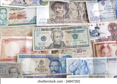 Old cash money from different countries around the world. With a twenty dollar US dollar bill on top.