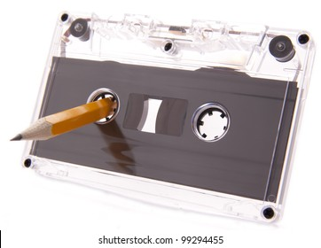 Old cassette tape isolated over a white background with pencil for rewind