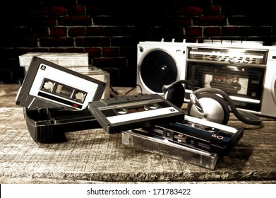 Old cassette tapes and cassette player on wooden surface