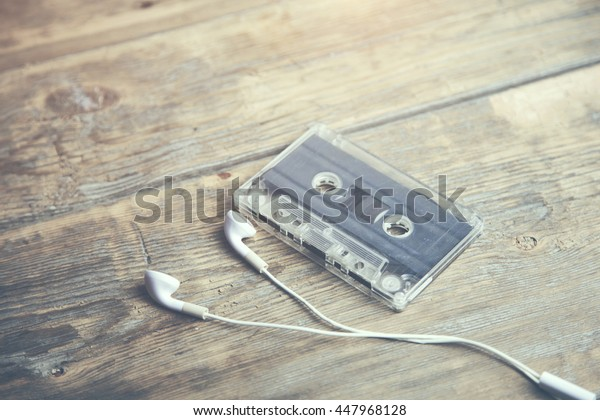 old cassettes tape with Earphone on wooden background