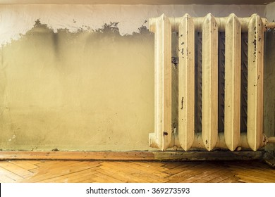old cast iron radiators with peeling paint on the wall