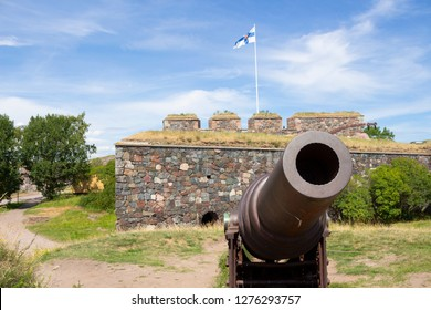 An old cast-iron artillery cannon and granite old fortifications on Suomenlinna fort island are overgrown with grass on a sunny summer day in Finland, and the flag of Finland is on the ancient walls.
