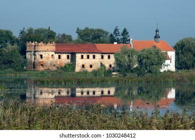 Old castle on bank of lake among tree in Starokostiantyniv, Khmelnytskyi region in Ukraine. Horizontal outdoors shot.