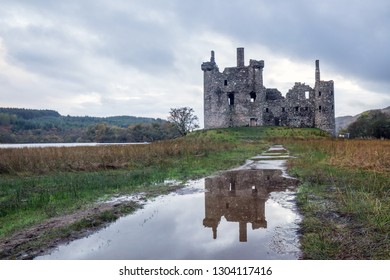 Old castle on the hill reflecting in the water, colorful autumn around and overcast weather