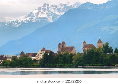 Old castle on Zurich lake with Alps mountains in background, Switzerland