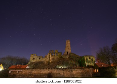 Old castle ruin under blue sky full of stars at night.