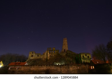 Old castle ruin under sky with stars at night.