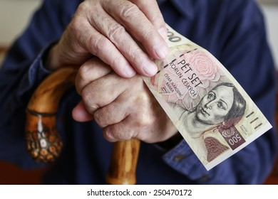 old caucasian man with a cane and czech money