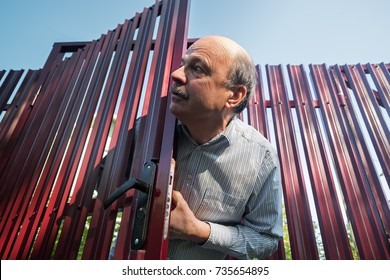 Old caucasian man with mustache carefully watches and looks from behind the fence, opening door. He is suspecting something is wrong