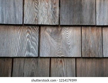 Old cedar siding shingles close up with wood patterns.